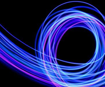 Light painting photography, long exposure photo of purple and blue streaks of vibrant color against a black background